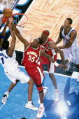 Dikembe Mutombo of the Atlanta Hawks goes up to block a shot by Tracy McGrady of the Orlando Magic during an NBA game in 2001 at the TD Waterhouse...