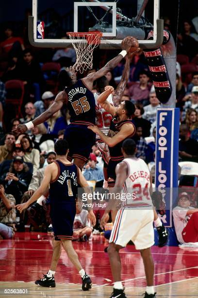 Dikembe Mutombo of the Denver Nuggets goes up to block a shot against the Los Angeles Clippers during an NBA game circa 1995 at the LA Sports Arena...