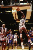 Dikembe Mutombo of the Georgetown Hoyas makes a dunk during a basketball game against the Depaul Blue Demons at Capital Centre on February 15 1990 in...
