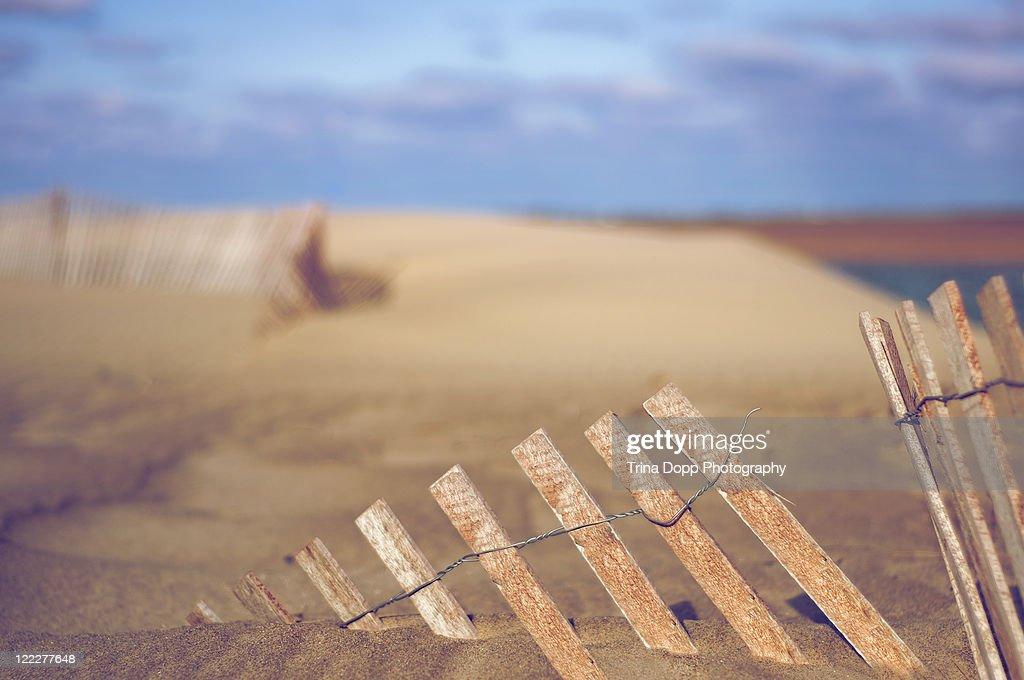 Dilapidated beach fence sinking in sand
