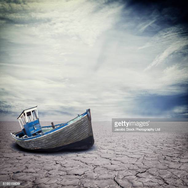 Dilapidated boat on dry cracked river bed