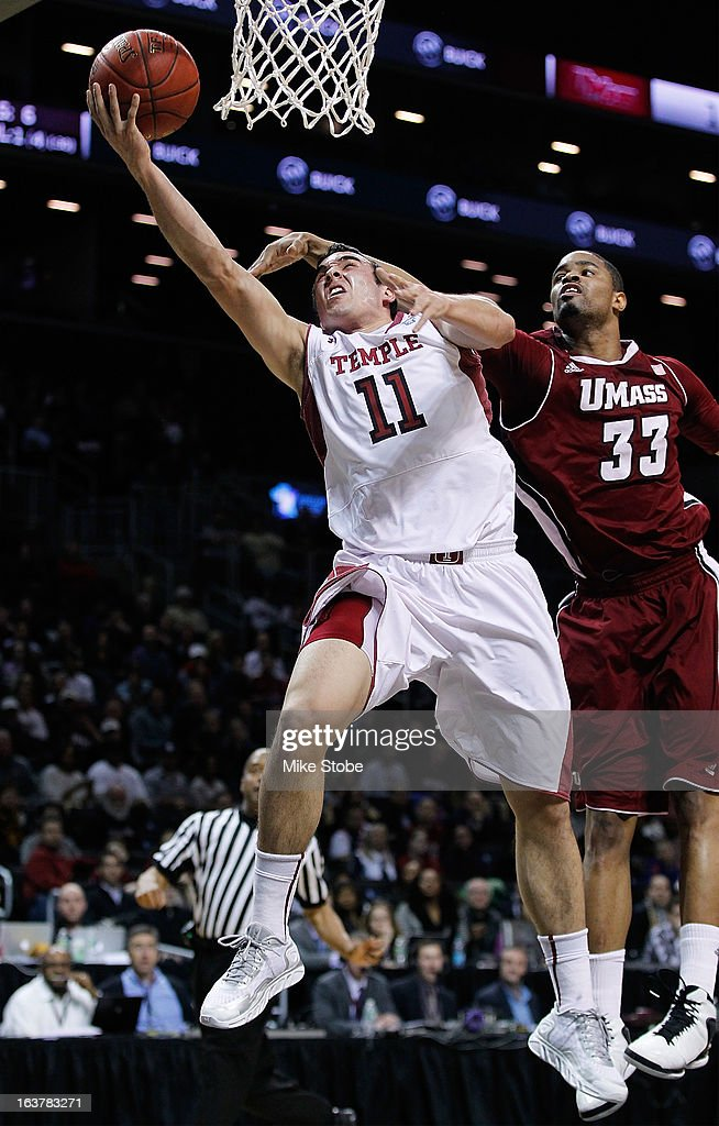 T.J. DiLeo #11 of the Temple Owls drives to the net against Terrell Vinson #33 of the Massachusetts Minutemen during the Quarterfinals of the Atlantic 10 Basketball Tournament at Barclays Center on March 15, 2013 in the Brooklyn borough of New York City.Massachusetts Minutemen defetaed the Temple Owls 79-74.