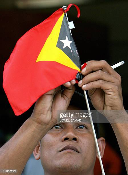 An East Timorese man sets a national flag at his car in Dili 26 May 2006 Tense calm prevailed in the capital of East Timor as Australian troops took...
