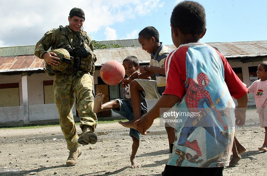 An international peacekeeping soldier from Australia plays football with children at a refugee camp Dili, 29 June 2007. East Timor's voters head to ballot boxes on 30 June to choose a new government tasked with uniting a violence-weary population yet to savour the fruits of the nation's five-year-old independence. After a mostly peaceful month of campaigning, the polls are expected to be a fierce contest between the parties of two former political allies: the bearded and dashing independence hero, Xanana Gusmao, and aloof former prime minister, Mari Alkatiri.