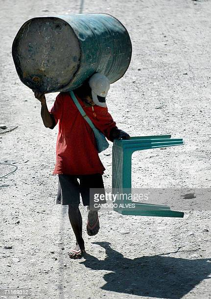 An man carries plundered items a rival's houses in Dili 10 June 2006 The Australianled multinational peacekeeping force is prepared to disarm and...