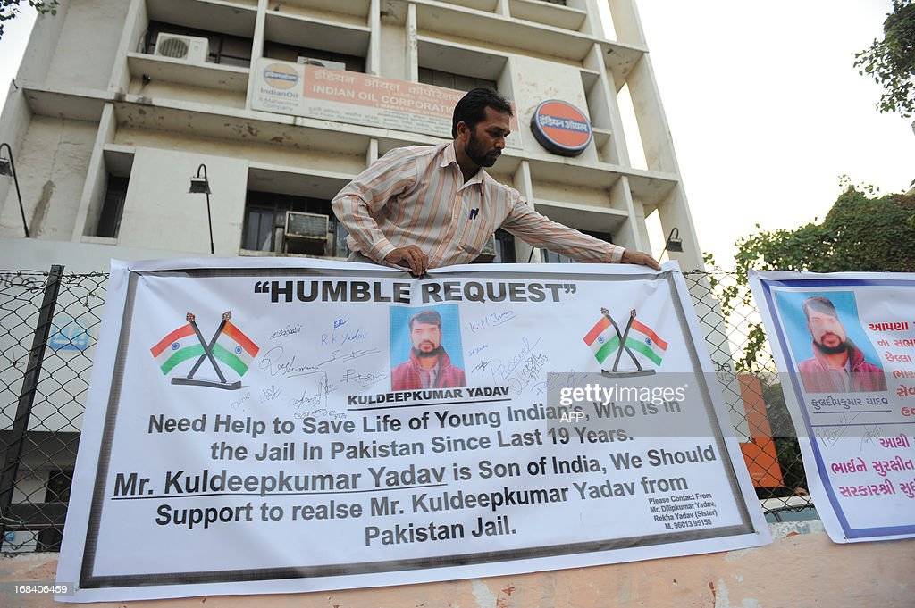 Dilipkumar Yadav (R) adjusts a banner with signatures calling for the release of his Indian brother, Kuldipkumar Yadav in Ahmedabad on May 9, 2013. The family members began a signature campaign to request the Indian authorities secure an early release of their brother Kuldipkumar Yadav, who is in the Kot Lakhpat Jail in Lahore, Pakistan since 1994 on charges of espionage. The family is worried for Kuldip's safety because of the to the recent killing of Indian prisoner Sarabjit Singh who was in the same jail. AFP PHOTO / Sam PANTHAKY