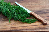 fresh dill and knife on a wooden cutting board