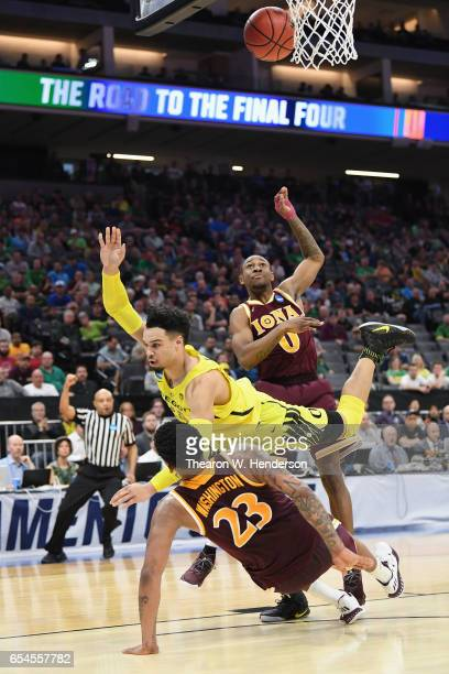 Dillon Brooks of the Oregon Ducks falls as he shoots the ball against Jordan Washington of the Iona Gaels in the first half during the first round of...