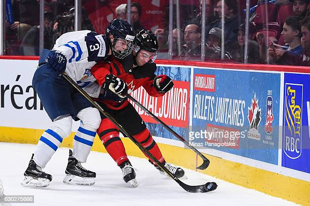 Dillon Dube of Team Canada and Urho Vaakanainen of Team Finland chase the puck into the boards during the IIHF exhibition game at the Bell Centre on...