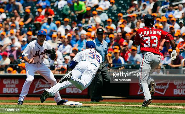 Dillon Gee of the New York Mets flips the ball to teammate Josh Satin at first base for a second inning out against Roger Bernadina of the Washington...