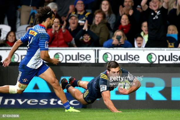 Dillon Hunt of the Otago Highlanders dives to score a try during the Super Rugby match between the Otago Highlanders of New Zealand and the Western...