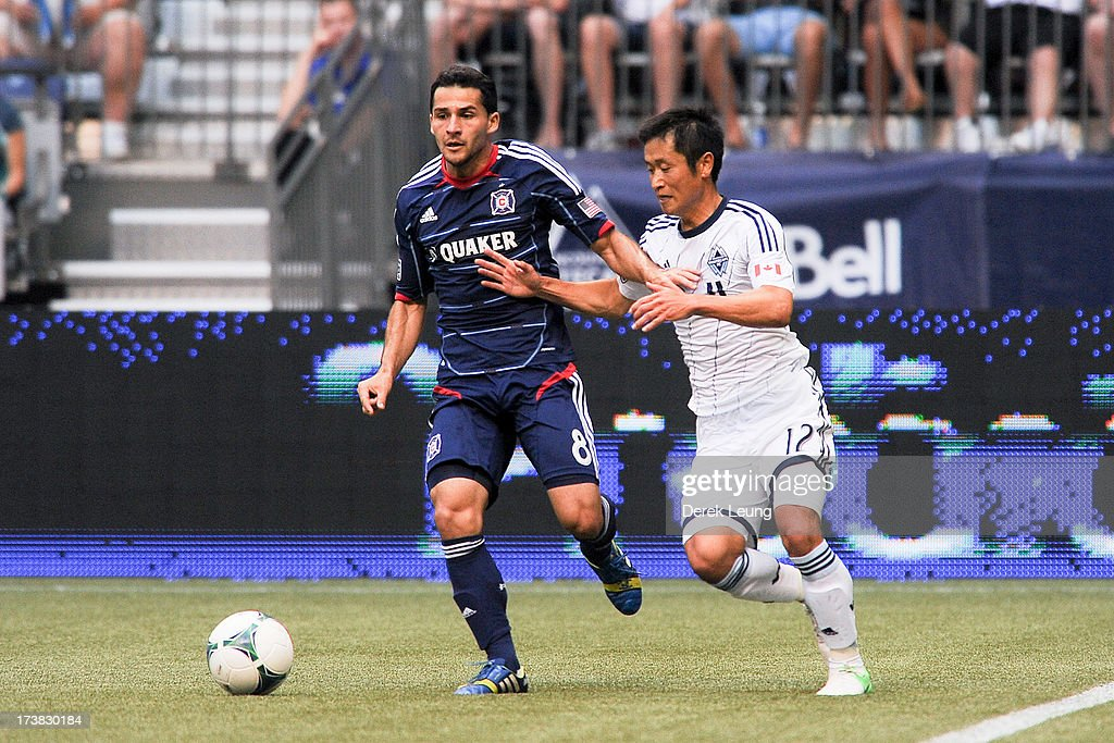 Dilly Duka of Chicago Fire chases the ball against YoungPyo Lee of the Vancouver Whitecaps during an MLS Match at BC Place on July 14 2013 in...