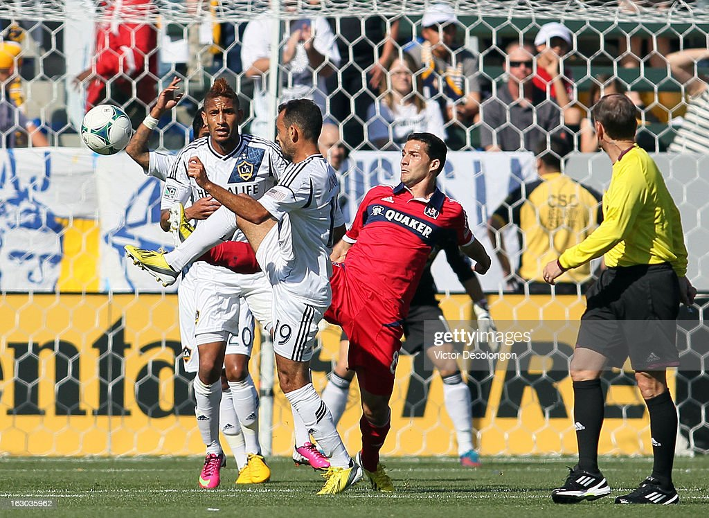 Dilly Duka #8 of the Chicago Fire and Juninho #19 of the Los Angeles Galaxy vie for the ball as Sean Franklin #5 of the Los Angeles Galaxy and referee Kevin Stott look on during the MLS match at The Home Depot Center on March 3, 2013 in Carson, California. The Galaxy defeated the Fire 4-0.