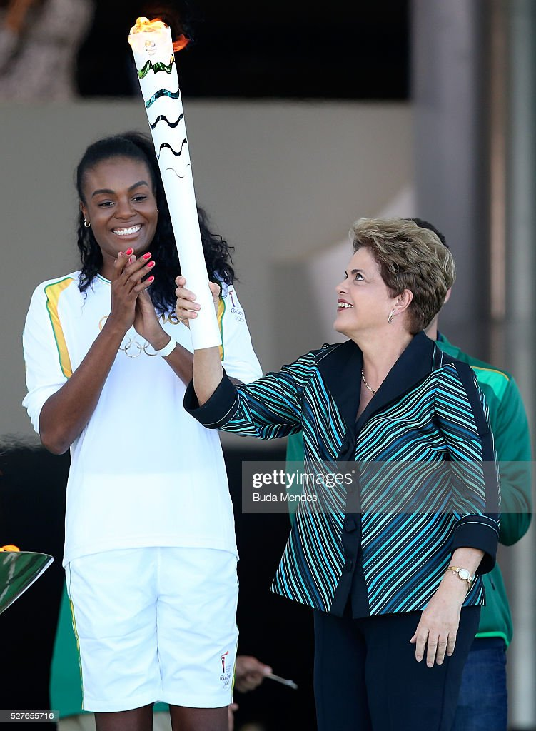 <a gi-track='captionPersonalityLinkClicked' href=/galleries/search?phrase=Dilma+Rousseff&family=editorial&specificpeople=1955968 ng-click='$event.stopPropagation()'>Dilma Rousseff</a>, President of Brazil, hands the Olympic torch to the first torch bearer Brazilian volleyball player <a gi-track='captionPersonalityLinkClicked' href=/galleries/search?phrase=Fabiana+Claudino&family=editorial&specificpeople=2151767 ng-click='$event.stopPropagation()'>Fabiana Claudino</a> on the ramp of the Palacio do Planalto on May 3, 2016 in Brasilia, Brazil. The Olympic torch will pass through 329 cities from all states from the north to the south of Brazil, until arriving in Rio de Janeiro on August 5, to lit the cauldron.