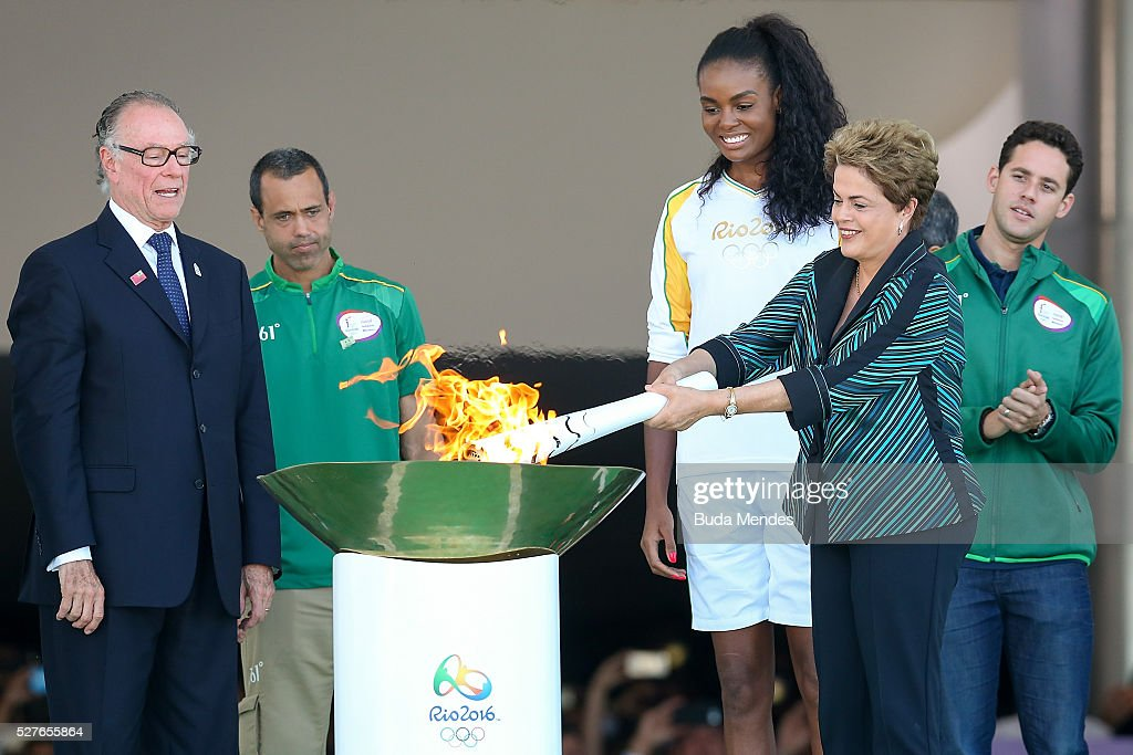<a gi-track='captionPersonalityLinkClicked' href=/galleries/search?phrase=Dilma+Rousseff&family=editorial&specificpeople=1955968 ng-click='$event.stopPropagation()'>Dilma Rousseff</a>, President of Brazil, lights the Olympic torch with Brazilian Olympic Committee Carlos Nuzman (L) and first torch bearer, volleyball player <a gi-track='captionPersonalityLinkClicked' href=/galleries/search?phrase=Fabiana+Claudino&family=editorial&specificpeople=2151767 ng-click='$event.stopPropagation()'>Fabiana Claudino</a> at the Palacio do Planalto on May 3, 2016 in Brasilia, Brazil. The Olympic torch will pass through 329 cities from all states from the north to the south of Brazil, until arriving in Rio de Janeiro on August 5, to lit the cauldron.