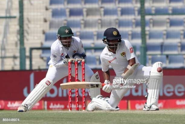 Dilruwan Perera of Sri Lanka plays a shot as Pakistan's wicketkeeper Safraz Ahmed looks on during the second day of their first Test cricket match at...