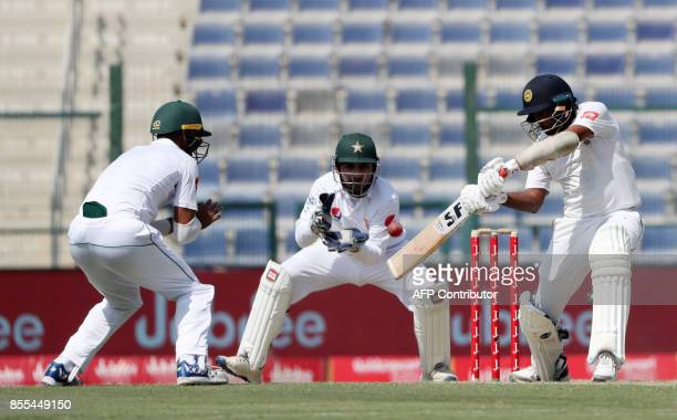 Dilruwan Perera of Sri Lanka plays a shot as Pakistan's wicketkeeper Safraz Ahmed looks on during the second day of the first Test cricket match at...