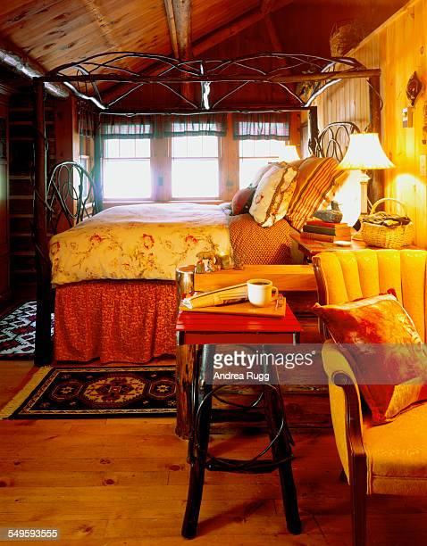 Dim lodge bedroom with intricate wood canopy bed