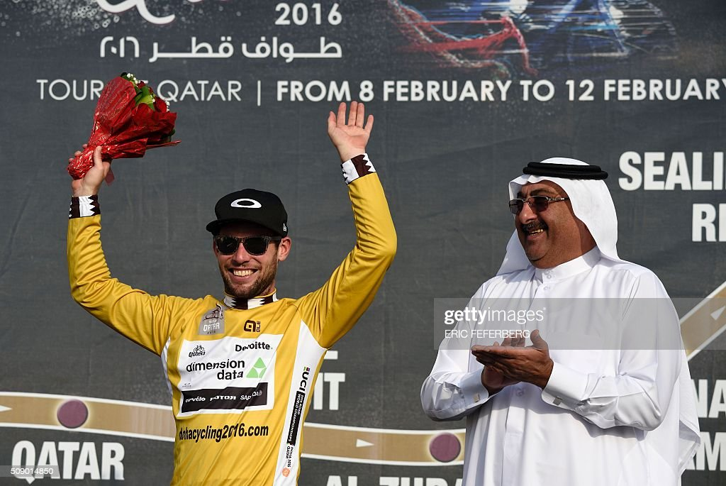 Dimension Data team leader, Britain's Mark Cavendish, celebrates on the podium after receiving the golden jersey from the President of the Qatari Cycling Federation, Sheikh Khaled bin Ali al-Thani (R) on February 8, 2016, at the end of the first stage of the 2016 Tour of Qatar between Dukhan and Al Khor Corniche, north of the Qatari capital Doha. Cavendish, the former world road race champion, took the gold jersey and covered the 175 kilometres from Dukhan to the Al Khor corniche in 3hrs 28.31secs, eight seconds in front of Modolo and 11 seconds ahead of Guardini. / AFP / ERIC FEFERBERG