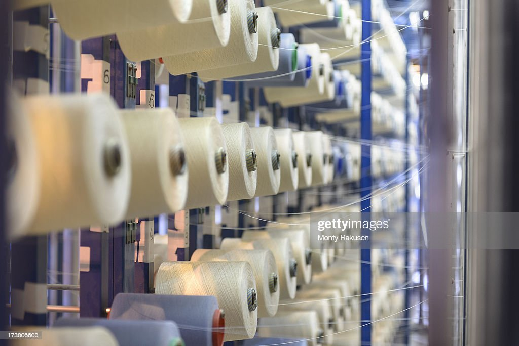 Diminishing perspective of rows of bobbins of thread in textile mill