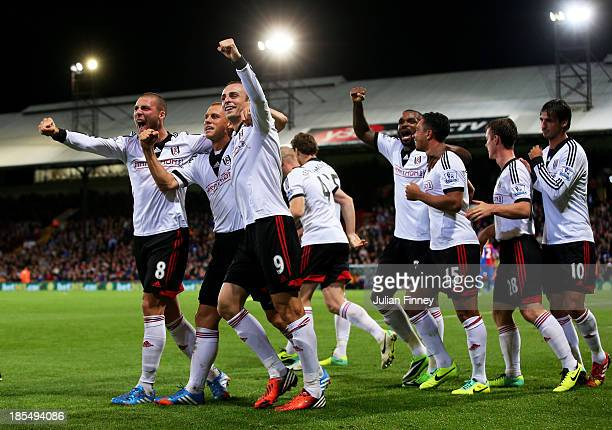 Dimitar Berbatov of Fulham celebrates with teammates Steve Sidwell and Pajtim Kasami after scoring his team's third goal during the Barclays Premier...