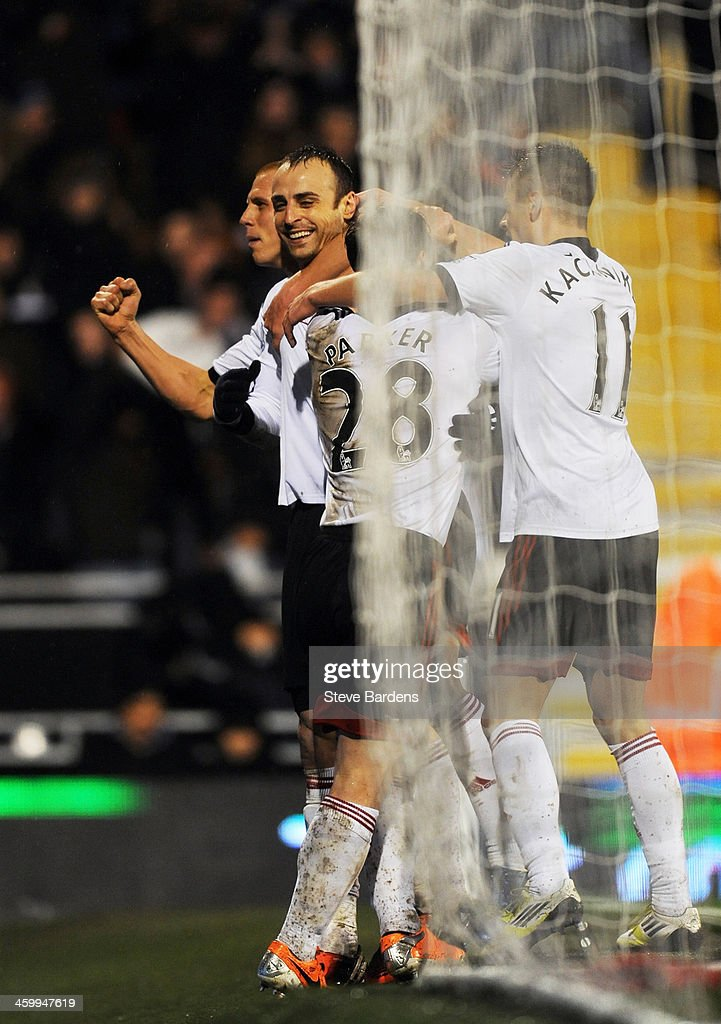 <a gi-track='captionPersonalityLinkClicked' href=/galleries/search?phrase=Dimitar+Berbatov&family=editorial&specificpeople=216379 ng-click='$event.stopPropagation()'>Dimitar Berbatov</a> (L) of Fulham is congratulated by teammates after scoring his team's second goal during the Barclays Premier League match between Fulham and West Ham United at Craven Cottage on January 1, 2014 in London, England.