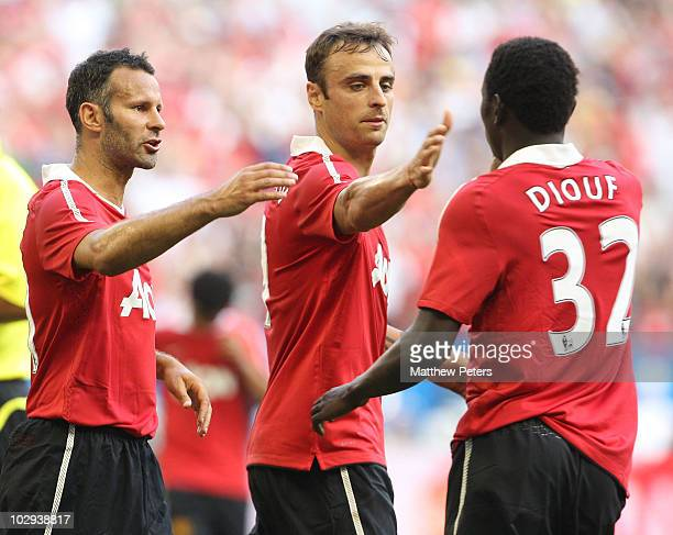 Dimitar Berbatov of Manchester United celebrates scoring their first goal during the preseason friendly against Celtic with Ryan Giggs and Mame Biran...