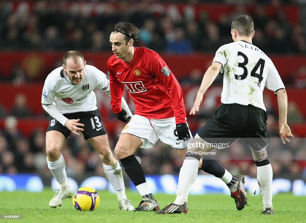 Dimitar Berbatov of Manchester United clashes with Danny Murphy and Chris Baird of Fulham during the Barclays Premier League match between Manchester...