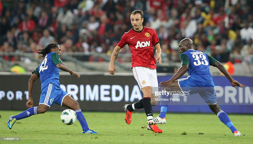 Dimitar Berbatov of Manchester United clashes with Tsweu Piet Mokoro (L) and Carlington Nyadombo of AmaZulu FC during the pre-season friendly between AmaZulu FC and Manchester United at Moses Mabhida Stadium on July 18, 2012 in Durban, South Africa.