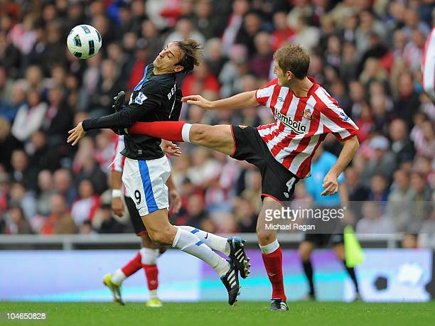 Dimitar Berbatov of Manchester United is challenged by Michael Turner of Sunderland during the Barclays Premier League match between Sunderland and...