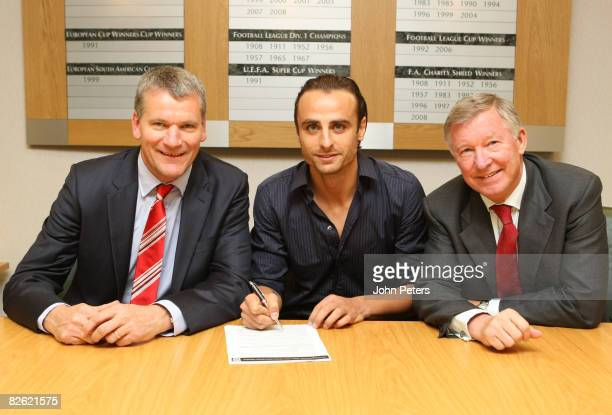 Dimitar Berbatov poses with manager Sir Alex Ferguson and Chief Executive David Gill of Manchester United after signing for the club at Old Trafford...