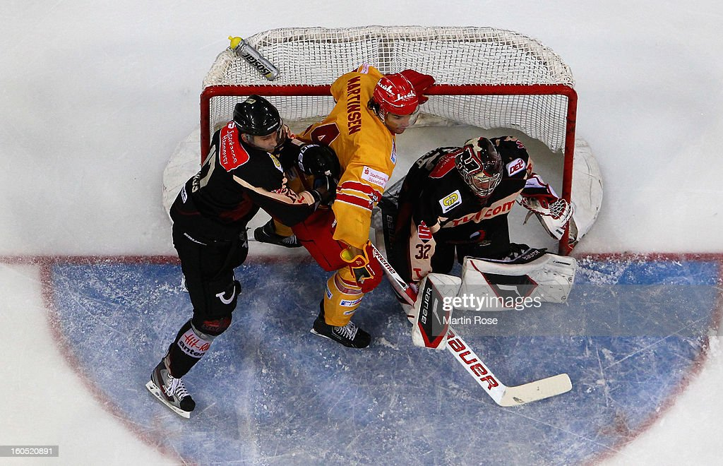 <a gi-track='captionPersonalityLinkClicked' href=/galleries/search?phrase=Dimitri+Paetzold&family=editorial&specificpeople=851119 ng-click='$event.stopPropagation()'>Dimitri Paetzold</a> (R), goaltender of Hannover blocks Andreas Martinsen (C) of Duesseldorf during the DEL match between Hannover Scorpions and Duesseldorfer EG at TUI Arena on February 1, 2013 in Hanover, Germany.