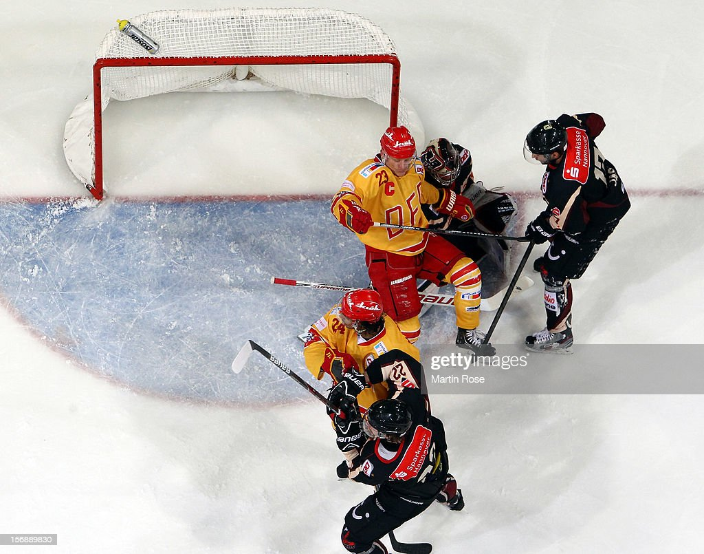 <a gi-track='captionPersonalityLinkClicked' href=/galleries/search?phrase=Dimitri+Paetzold&family=editorial&specificpeople=851119 ng-click='$event.stopPropagation()'>Dimitri Paetzold</a> (C), goaltender of Hannover checks <a gi-track='captionPersonalityLinkClicked' href=/galleries/search?phrase=Daniel+Kreutzer&family=editorial&specificpeople=239202 ng-click='$event.stopPropagation()'>Daniel Kreutzer</a> (#23) of Duesseldorf in front of the net during the DEL match between Hannover Scorpions and Duesseldorfer EG at TUI Arena on November 23, 2012 in Hanover, Germany.