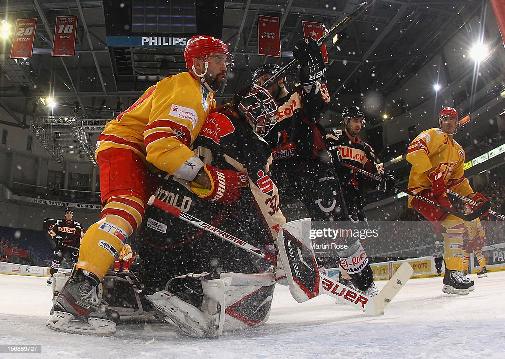 <a gi-track='captionPersonalityLinkClicked' href=/galleries/search?phrase=Dimitri+Paetzold&family=editorial&specificpeople=851119 ng-click='$event.stopPropagation()'>Dimitri Paetzold</a> (R), goaltender of Hannover makes a save on Ashton Rome (L) of Duesseldorf during the DEL match between Hannover Scorpions and Duesseldorfer EG at TUI Arena on November 23, 2012 in Hanover, Germany.