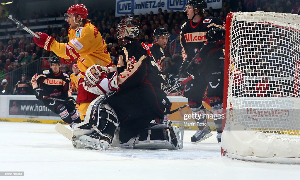 Dimitri Paetzold (R), goaltender of Hannover makes a save on Carl Ridderwall (C) of Duesseldorf during the DEL match between Hannover Scorpions and Duesseldorfer EG at TUI Arena on November 23, 2012 in Hanover, Germany.