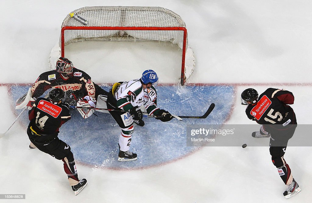 Dimitri Paetzold goaltender of Hannover makes a save on Daryl Boyle of Augsburg during the DEL match between Hannover Scorpions and Augsburger...