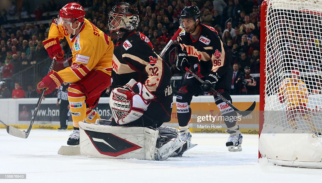 Dimitri Paetzold (R), goaltender of Hannover makes a save on Manuel Strobel (L) of Duesseldorf during the DEL match between Hannover Scorpions and Duesseldorfer EG at TUI Arena on November 23, 2012 in Hanover, Germany.