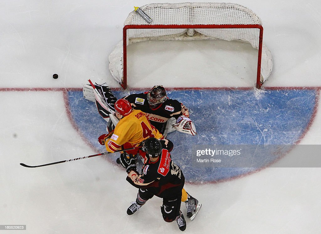 <a gi-track='captionPersonalityLinkClicked' href=/galleries/search?phrase=Dimitri+Paetzold&family=editorial&specificpeople=851119 ng-click='$event.stopPropagation()'>Dimitri Paetzold</a> (R), goaltender of Hannover saves the shot of Ashton Rome (#44) of Duesseldorf during the DEL match between Hannover Scorpions and Duesseldorfer EG at TUI Arena on February 1, 2013 in Hanover, Germany.