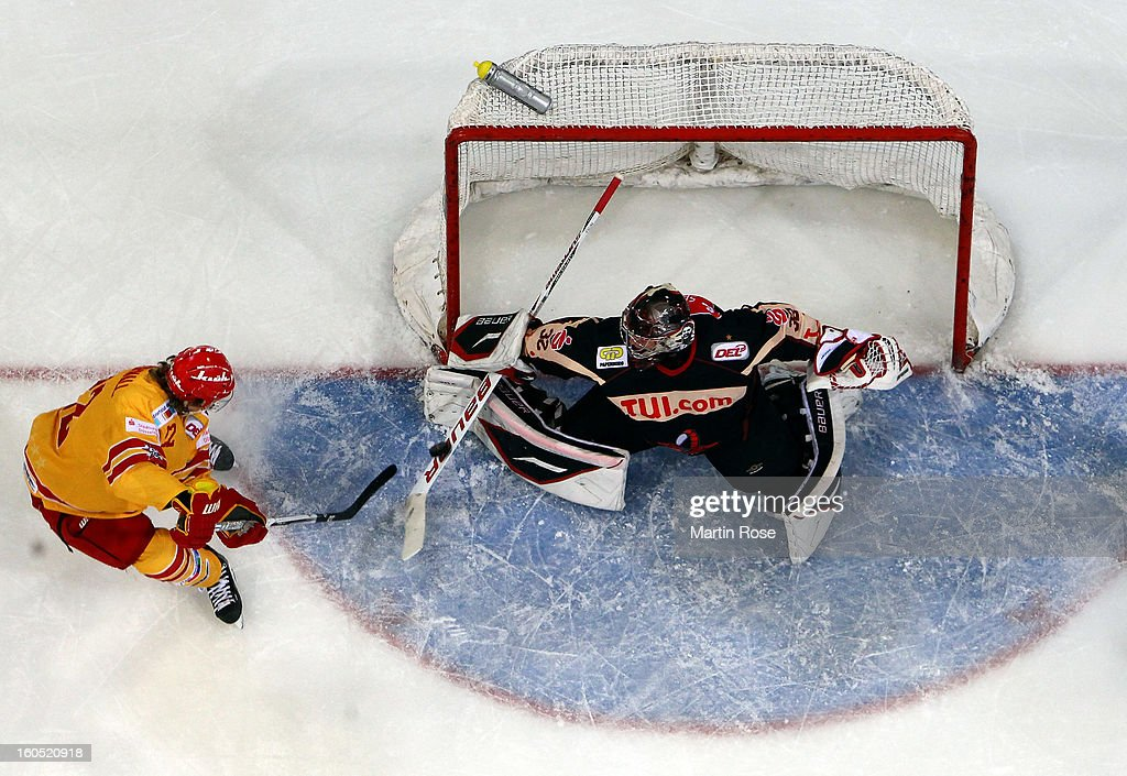 <a gi-track='captionPersonalityLinkClicked' href=/galleries/search?phrase=Dimitri+Paetzold&family=editorial&specificpeople=851119 ng-click='$event.stopPropagation()'>Dimitri Paetzold</a> (R), goaltender of Hannover saves the shot of Carl Ridderwall (L) of Duesseldorf during the DEL match between Hannover Scorpions and Duesseldorfer EG at TUI Arena on February 1, 2013 in Hanover, Germany.