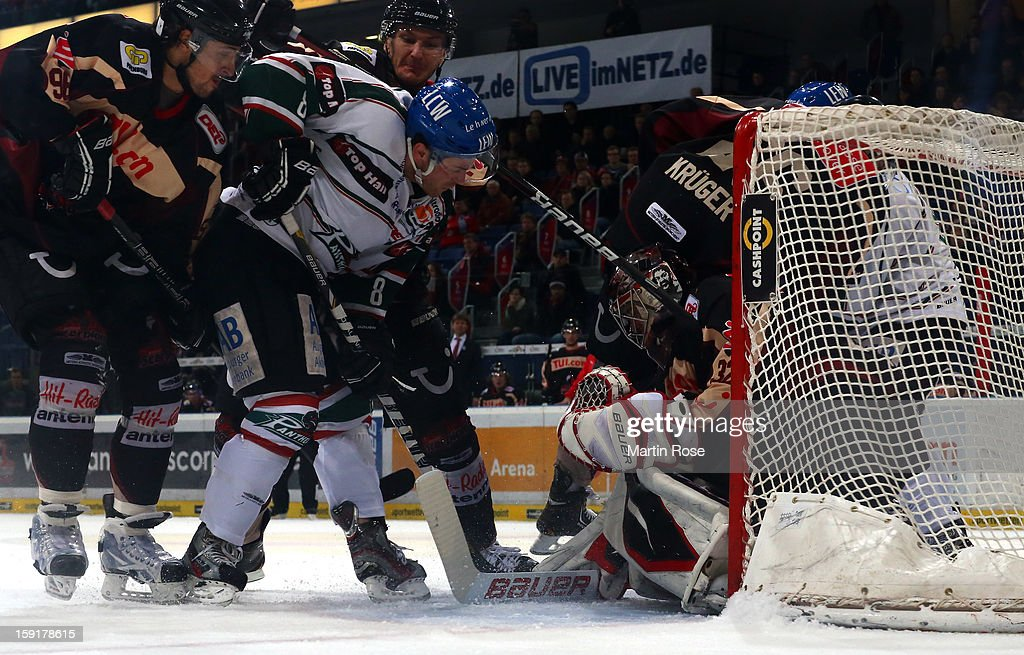 Dimitri Paetzold (R), goaltender of Hannover saves the shot of Sergio Somma (C) of Augsburg battle for the puck during the DEL match between Hannover Scorpions and Augsburger Panther at TUI Arena at TUI Arena on January 9, 2013 in Hanover, Germany.