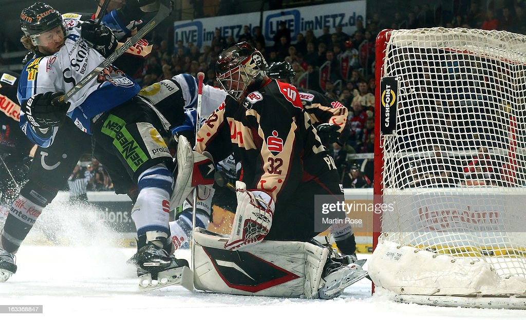Dimitri Paetzold goaltender of Hannover stops Karl Stewart of Straubing in front of the net during the DEL match between Hannover Scorpions and...