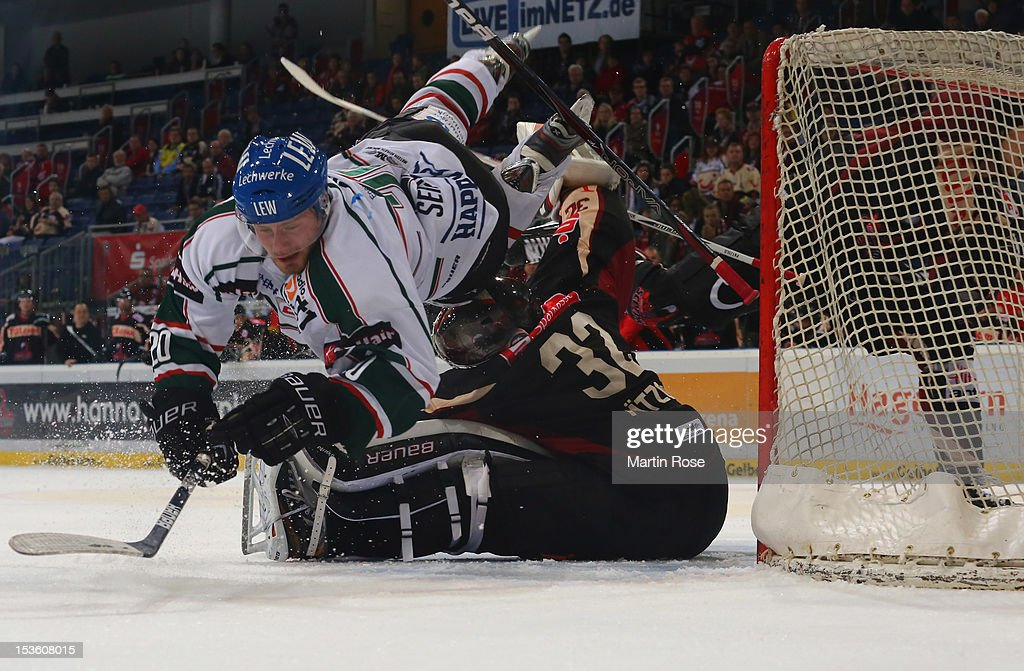 Dimitri Paetzold goaltender of Hannover stops Patrick Seifert of Augsburg battle in front of the net during the DEL match between Hannover Scorpions...
