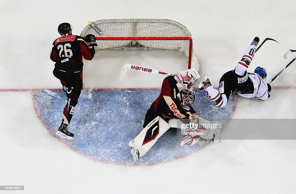 Dimitri Paetzold goaltender of Hannover stops Patrick Seifert of Augsburg in front of the net during the DEL match between Hannover Scorpions and...