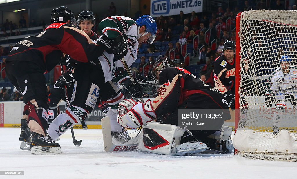 Dimitri Paetzold goaltender of Hannover stops Sergio Somma of Augsburg battle in front of the net during the DEL match between Hannover Scorpions and...