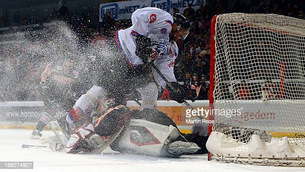 Dimitri Paetzold goaltender of Hannover stops Steven Rupprich of Nuernberg in front of the net during the DEL match between Hannover Scorpions and...
