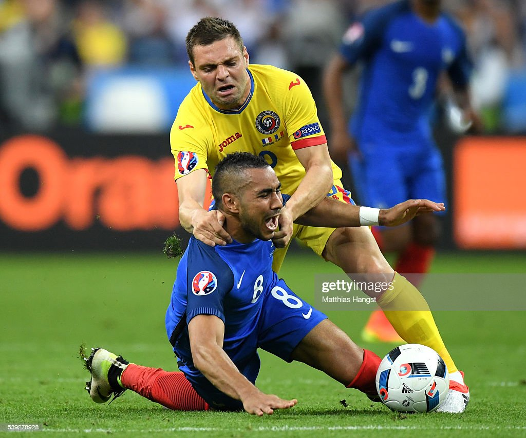 Dimitri Payet of France is chellenged by Adrian Popa of Romania during the UEFA Euro 2016 Group A match between France and Romania at Stade de France on June 10, 2016 in Paris, France.