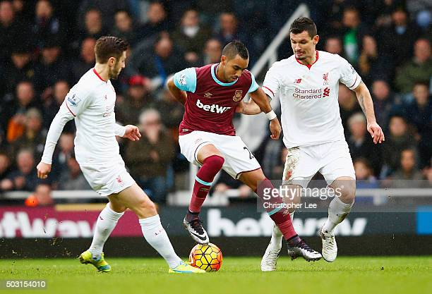 Dimitri Payet of West Ham United competes for the ball against Adam Lallana and Dejan Lovren of Liverpool during the Barclays Premier League match...