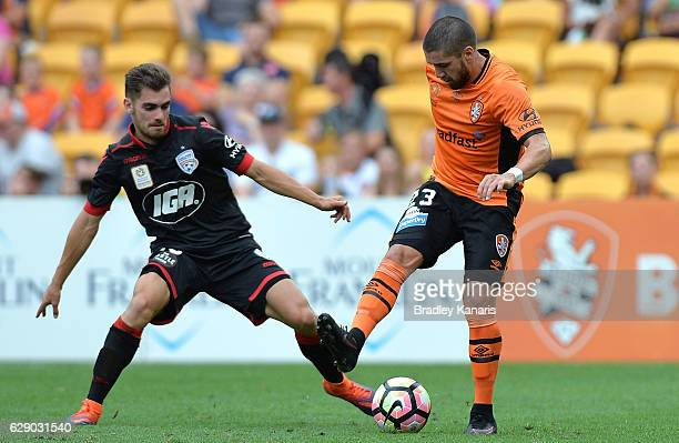 Dimitri Petratos of the Roar and Benjamin Garuccio of Adelaide compete for the ball during the round 10 ALeague match between the Brisbane Roar and...