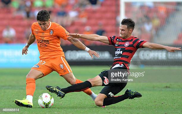 Dimitri Petratos of the Roar attempts to get past the defence of Mark Bridge of the Western Sydney Wanderers during the round 20 ALeague match...