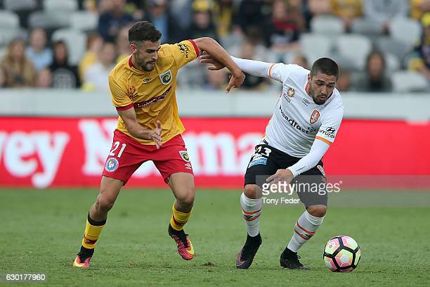 Dimitri Petratos of the Roar contests the ball with Michael Neill of the Mariners during the round 11 ALeague match between the Central Coast...